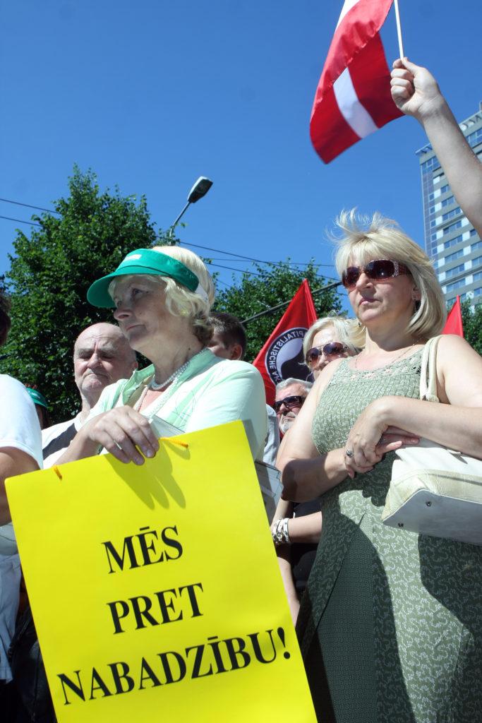 """Latvijas Brīvo arodbiedrību savienības (LBAS) organizētā mītiņa """"Par sociālo taisnīgumu – pret nabadzību!"""" dalībnieces pie Ministru kabineta valdībai atgādina par LBAS prasībām – par cienīga darba un dzīves apstākļiem Latvijā."""