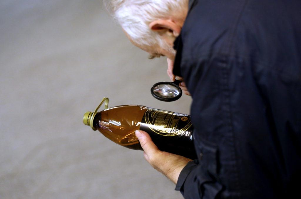 Vīrietis lasa alus pudeles etiķeti.