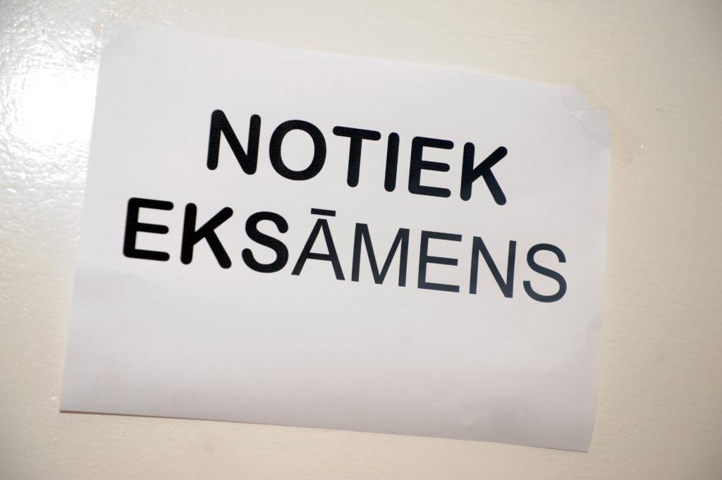 """Lapa ar uzrakstu """"Notiek eksāmens"""" Rīgas Šampētera vidusskolā."""