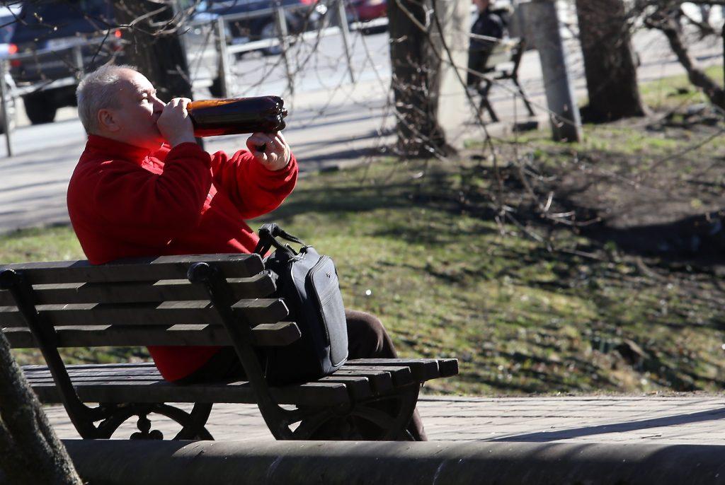 Vīrietis parkā uz soliņa.