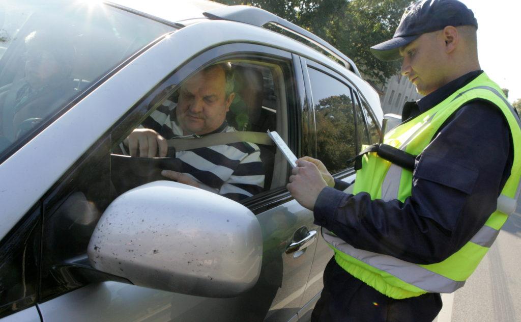"""Ceļu policists pārbauda automašīnas vadītāja dokumentus satiksmes drošības kampaņas """"Redzi jostu – sprādzējies!"""" ietvaros organizētajā reidā, kura laikā pārbauda vai autovadītāji, to blakussēdētāji un jo īpaši aizmugurē sēdošie pasažieri ir piesprādzējušies."""