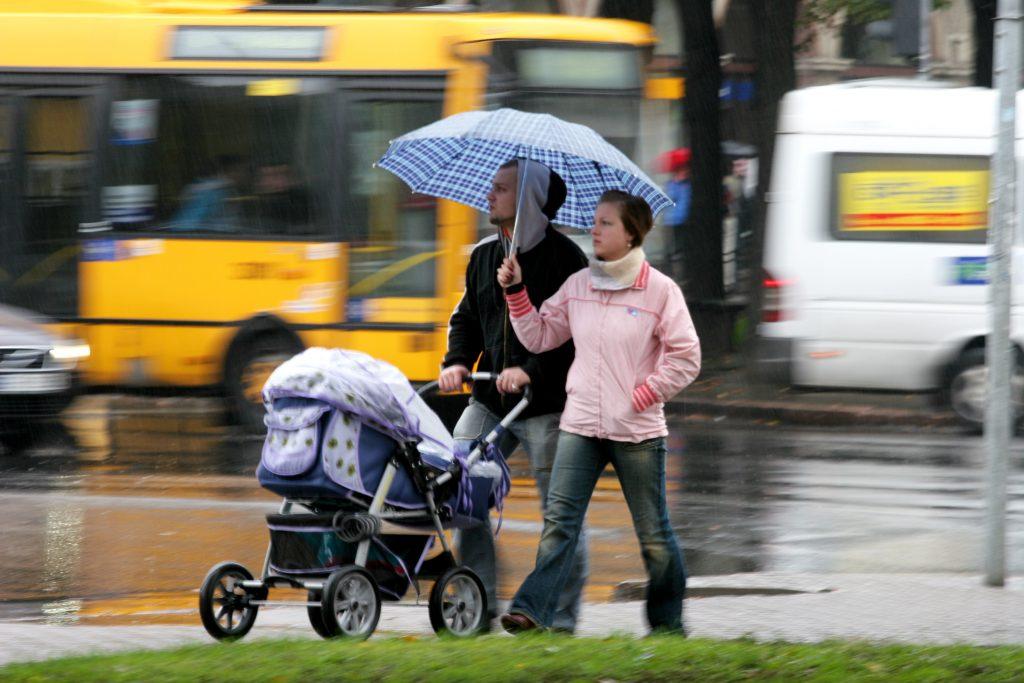 Ģimene ar bērnu ratiņiem lietus laikā.